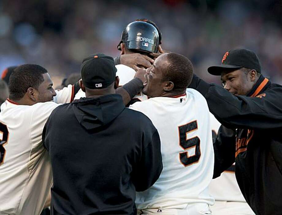 Andres Torres gets mobbed by his teammates after hitting the game-winning base hit deep into left field in the bottom of the 10th inning as the San Francisco Giant defeat the Florida Marlins 10-9 in 10 innings in San Francisco, Calif., on Wednesday, July 28, 2010. Photo: Chad Ziemendorf, The Chronicle