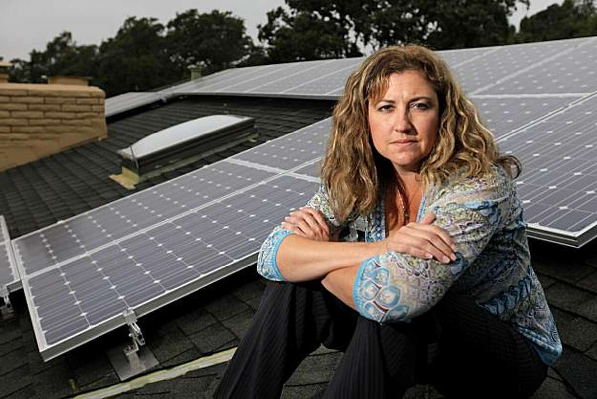 Renee Hyde sits on her roof where she had solar panels installed under the publicly-financed home retrofitting program, Tuesday July 27, 2010, in Santa Rosa, Calif. The program is now being blocked by Fannie and Freddie Mac.