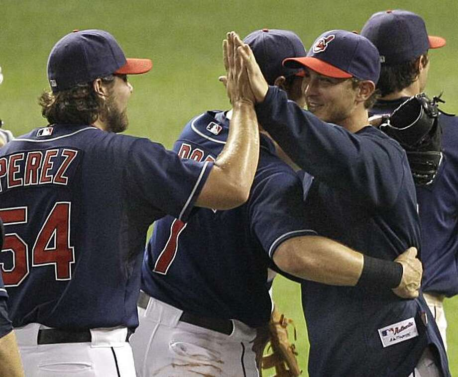 Cleveland Indians starting pitcher Josh Tomlin, right, is hugged by teammate Matt LaPorta and high-fived by Chris Perez after they beat the New York Yankees 4-1 in a baseball game in Cleveland on Tuesday, July 27, 2010.  Tomlin was the winning pitcher inhis Major League debut. Photo: Amy Sancetta, AP