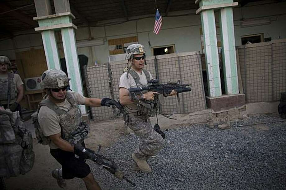 US soldiers from 1-320th Alpha Battery, 2nd Brigade of the 101st Airborne Division, run to firing positions after coming under attack by Taliban insurgents at COP Nolen, in the volatile Arghandab Valley, Kandahar, Afghanistan, Tuesday, July 27, 2010. Photo: Rodrigo Abd, Associated Press