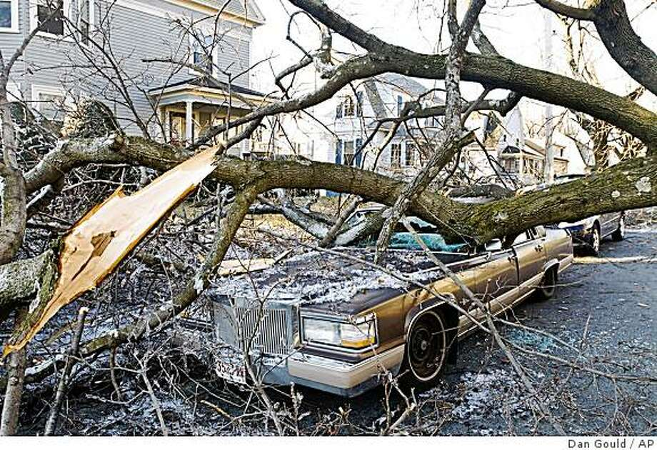 A tree felled during an ice storm lies on top of a car Saturday, Dec. 13, 2008, in Worcester, Mass. Utility crews worked through a night of hand-numbing cold in the Northeast but they still had a long way to go before restoring power to all of the more than 1 million homes and businesses blacked out by a huge ice storm. (AP Photo/The Telegram & Gazette, Dan Gould) Photo: Dan Gould, AP