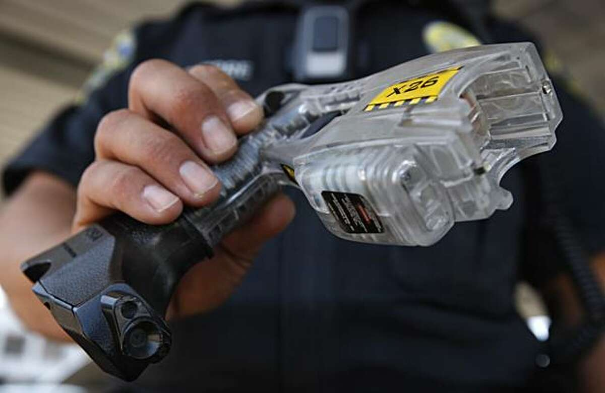 Police officer George Aguirre holds a Taser fitted with a video camera (lower left) in Brentwood, Calif., on Wednesday, July 21, 2010. The camera is activated every time police officers aim the electric stun gun.