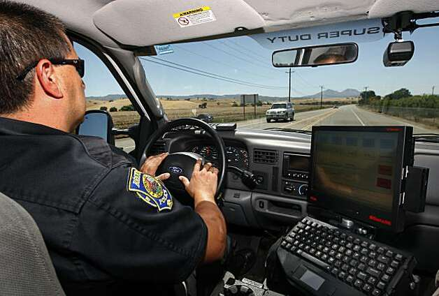 Police officer George Aquirre cruises down a rural road while on patrol in Brentwood, Calif., on Wednesday, July  21, 2010. All of the police cruisers in Brentwood have small video cameras (upper right) mounted on the wndshield which automatically record when the emergency lights are activated by the officer. Photo: Paul Chinn, The Chronicle