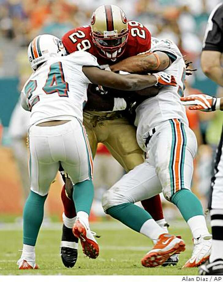San Francisco 49ers' DeShaun Foster is brought down by Miami Dolphins' Renaldo Hill (24) and Randy Starks in the second quarter of a football game in Miami, Sunday, Dec. 14, 2008. Photo: Alan Diaz, AP