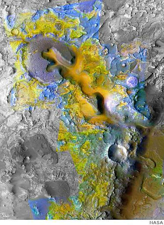 The color coding on this composite image of an area about 20 kilometers (12 miles) wide on Mars is based on infrared spectral information interpreted as evidence of various minerals present. Carbonate, which is indicative of a wet and non-acidic history, occurs in very small patches of exposed rock appearing green in this color representation, such as near the lower right corner.The scene is heavily eroded terrain to the west of a small canyon in the Nili Fossae region of Mars. It was one of the first areas where researchers on the Compact Reconnaissance Imaging Spectrometer for Mars (CRISM) science team detected carbonate in Mars rocks. The spectral information comes from infrared imaging by CRISM, one of six science instruments on NASA's Mars Reconnaissance Orbiter. That coloring is overlaid on a grayscale image from the same orbiter's Context Camera. Photo: NASA