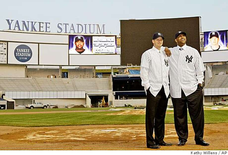 Pitchers A.J. Burnett, left, and CC Sabathia pose for photographers on the field at the new Yankee Stadium in New York, Thursday, Dec. 18, 2008. The free agents finalized their contracts with the New York Yankees. (AP Photo/Kathy Willens) Photo: Kathy Willens, AP