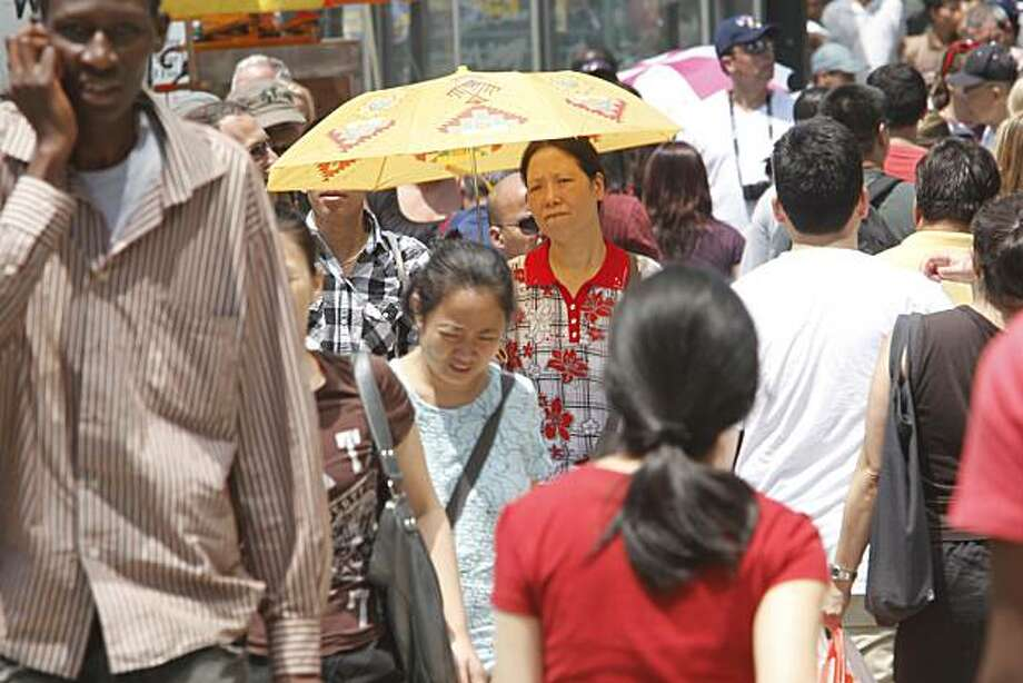 A woman uses an umbrella to shield herself from the sun while walking on Canal St. Saturday, July 17, 2010 in New York. Photo: Mary Altaffer, AP