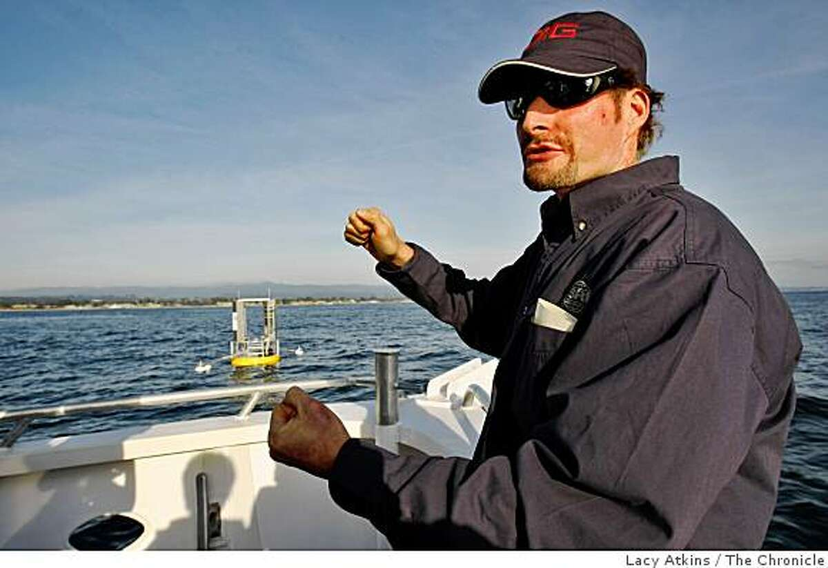 Roy Kornbluh of Stanford Research Institute explains the rubbery material that stretches and snaps back into place on the buoy which is located one mile outside the Santa Cruz Harbor, Monday Dec. 8, 2008, in Santa Cruz, Calif. Researchers show members of the media their new twist on generating electricity from the bobbing of the ocean wave through a buoy.