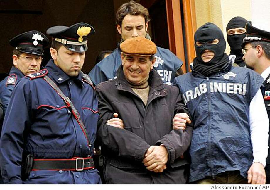 Italian Carabinieri paramilitary police officers escort a man identified as Giuseppe Scaduto, center, Tuesday, Dec. 16, 2008, one of the 100 suspected mobsters arrested in Palermo and in other Sicilian cities, Italy. Italian police backed by helicopters arrested almost 100 suspected mobsters Tuesday and thwarted a plan by the Sicilian Mafia to reconstitute itself and form a new ruling commission to set strategy, authorities said. Carabinieri police in Palermo said the operation there and in other Sicilian cities was one of the largest in recent years and gave investigators a picture of the new highest echelons of the Mafia. (AP Photo/Alessandro Fucarini) Photo: Alessandro Fucarini, AP