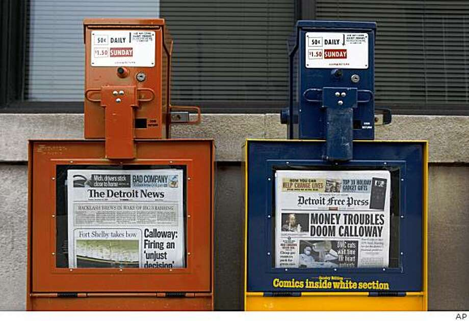 "Detroit Free Press and The Detroit News newspapers boxes are shown on the day the companies announced they plan to offer only three days of home delivery and will push their online editions in a fight for their survival amid slumping revenue industry wide during a news conference in Detroit, Tuesday, Dec. 16, 2008. The Detroit Media Partnership expects to cut about 9 percent of its work force but ""hopefully"" less. (AP Photo) Photo: AP"