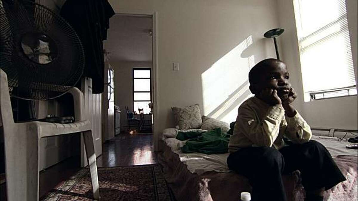 Christian Yoanson sits in his room in a scene from,