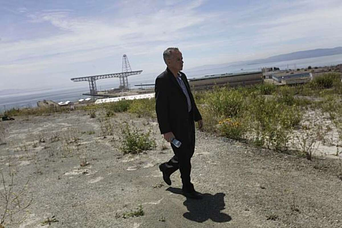 Michael Cohen, Director of Economic and Workforce Development for San Francisco, walks across the Hilltop community being developed on the Hunters Point Shipyard redevelopment project with the site of the proposed NFL stadium and other parts of the Hunters Point Shipyard redevelopment project behind him in San Francisco, Calif. on Wednesday June 2, 2010.
