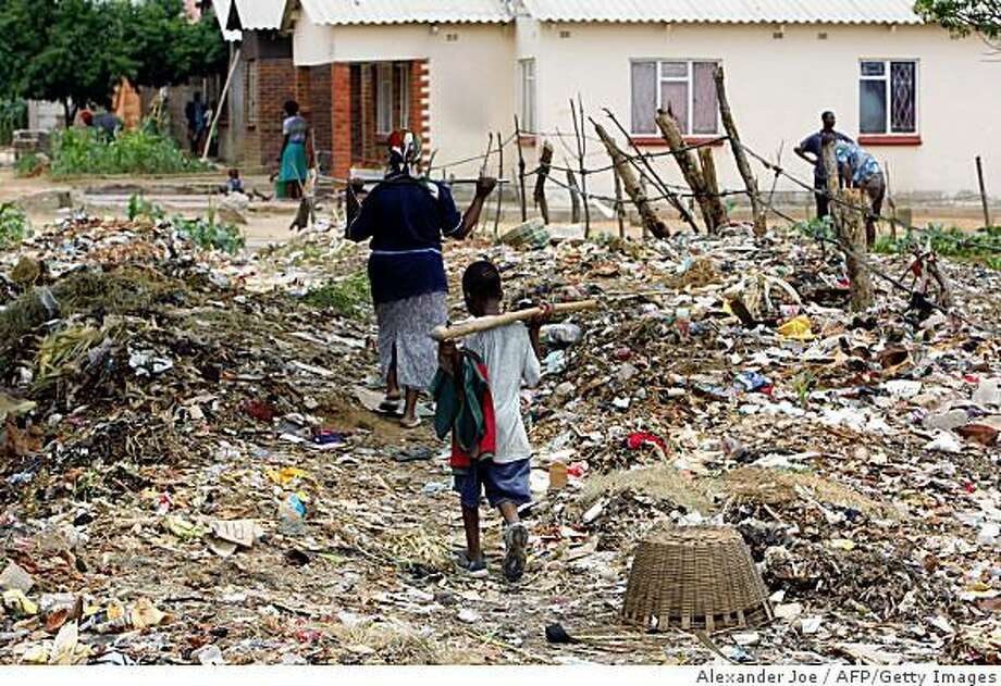 "A Zimbabwean woman and a child walk among garbage in Harare on December 13, 2008. US Secretary of State Condoleezza Rice was to hold talks next week with the UN on Zimbabwe, as Harare blamed Britain for a ""genocidal"" cholera outbreak and President Robert Mugabe ignored mounting calls to quit. Zimbabwe's crumbling infrastructure has helped spread the disease across the country, as broken water and sewage pipes have left many neighbourhoods without clean drinking water or adequate sanitation. AFP PHOTO / ALEXANDER JOE (Photo credit should read ALEXANDER JOE/AFP/Getty Images) Photo: Alexander Joe, AFP/Getty Images"
