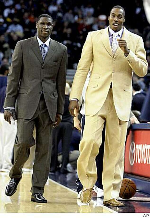 Orlando Magic's Dwight Howard, right, and Mickael Pietrus walk on the court during the first half of an NBA basketball game against the Golden State Warriors Monday, Dec. 15, 2008, in Oakland, Calif. (AP Photo) Photo: AP