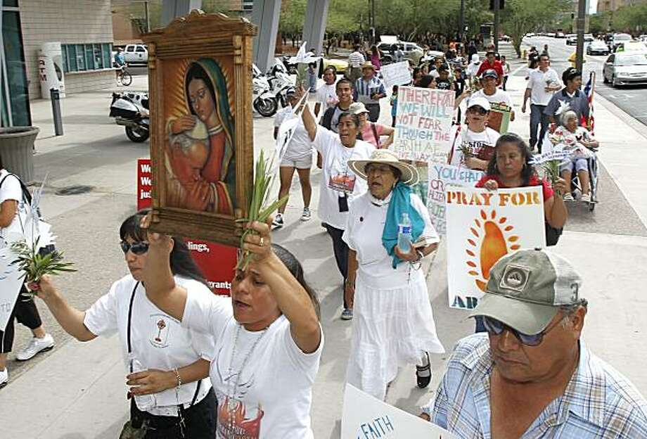 Dozens march to protest the SB1070 Arizona immigration law in front of U.S. District Court Thursday, July 22, 2010, in Phoenix.  U.S. District Judge Susan Bolton is holding multiple hearings on whether the new Arizona immigration law should take effect onJuly 29. Photo: Ross D. Franklin, AP