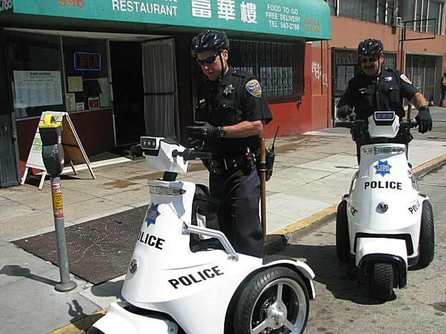 San Francisco Police Officers Eric Balmy and Julio Bandoni give their new electric scooters a spin. Photo: C.W. Nevius, The Chronicle