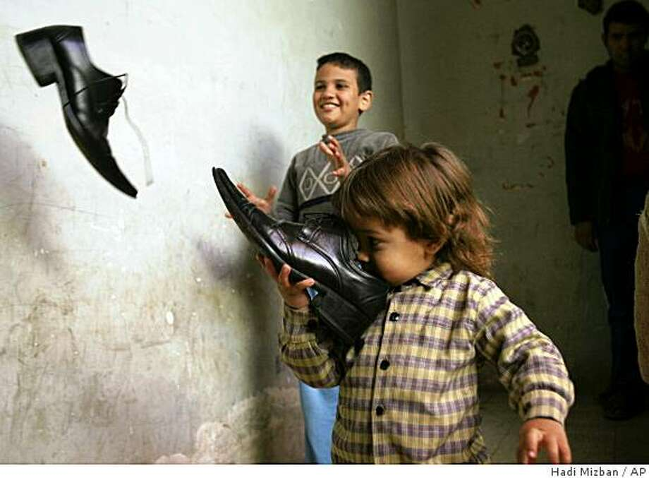Children play with shoes owned by Iraqi journalist Muntadar al-Zeidi outside his apartment in Baghdad, Iraq, Monday, Dec. 15, 2008.  The children are neighbors to al-Zeidi who threw his shoes at President George W. Bush during a press conference in Baghdad on Sunday, while yelling in Arabic.(AP Photo/Hadi Mizban) Photo: Hadi Mizban, AP