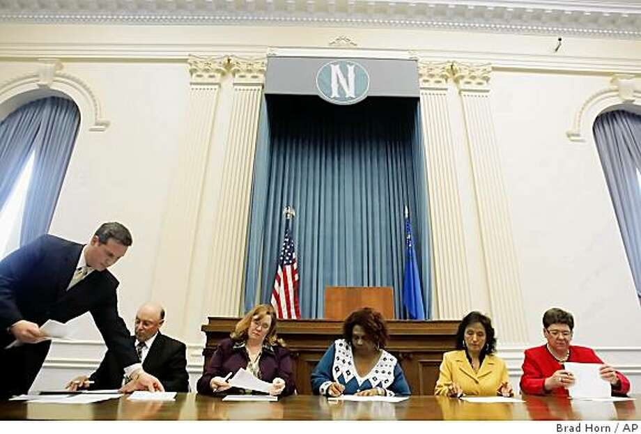 Nevada Secretary of State Ross Miller, standing left, presides over Nevada's five Electoral College members from left, Ronald Hibble, Sen. Maggie Carlton, D-Las Vegas, Ruby Duncan, Theresa Navarro, and Tahis Castro, at the Capitol building in Carson City, Nev., on Monday, Dec. 15, 2008. (AP Photo/Nevada Appeal, Brad Horn) Photo: Brad Horn, AP