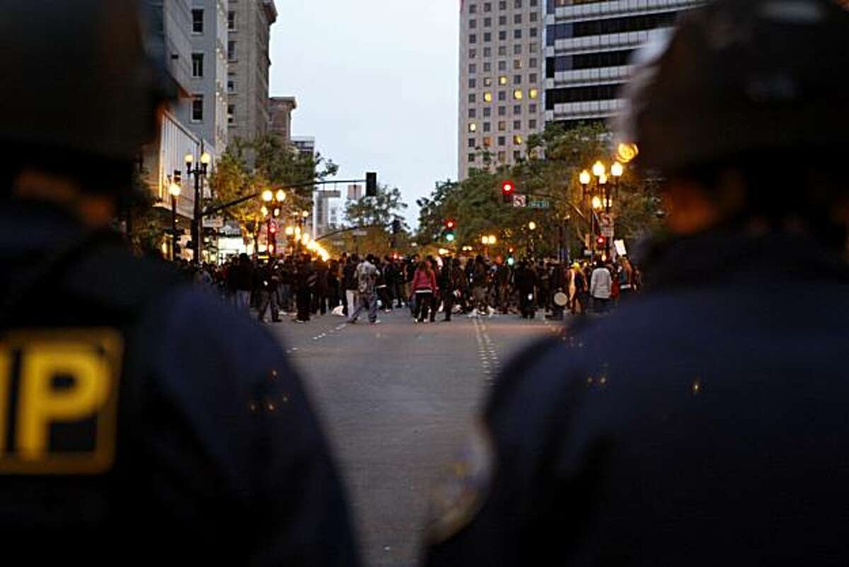 Police officers stand by as crowds of people loot the Foot Locker on Broadway Street following the Johannes Mehserle verdict on Thursday, July 8, 2010 in Oakland, Calif.