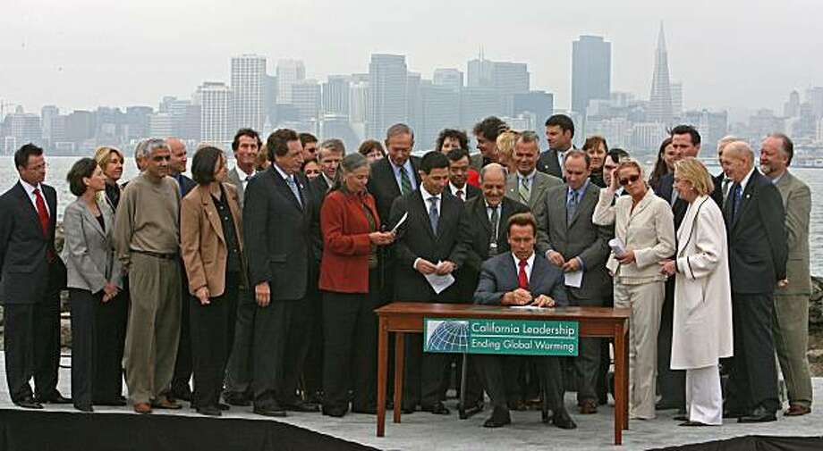 California became the first state to impose total caps on greenhouse gasses when Governor Arnold Schwarzenegger signed a sweeping global warming bill. The governor was joined in person by Democratic lawmakers and San Francisco Mayor Gavin Newsom during the signing ceremony on Treasure Island Wednesday morning. British Prime Minister Tony Blair also addressed the crowd through a satellite video hook-up, congratulating the governor and the legislature for passing such bold legislation. The law that resulted from a bi-partisan effort imposes a first-in-the-nation emissions cap on utilities, refineries and manufacturing plants in a bid to curb the gases scientists blame for warming the Earth. California's efforts on global warming have gained international attention since Schwarzenegger and the state's legislative Democrats reached an accord last month. The law hands the Republican governor a key victory in an election year where he has sought to portray himself as a friend to the environment.  9/28/06 {Frederic Larson} Photo: Frederic Larson, The Chronicle