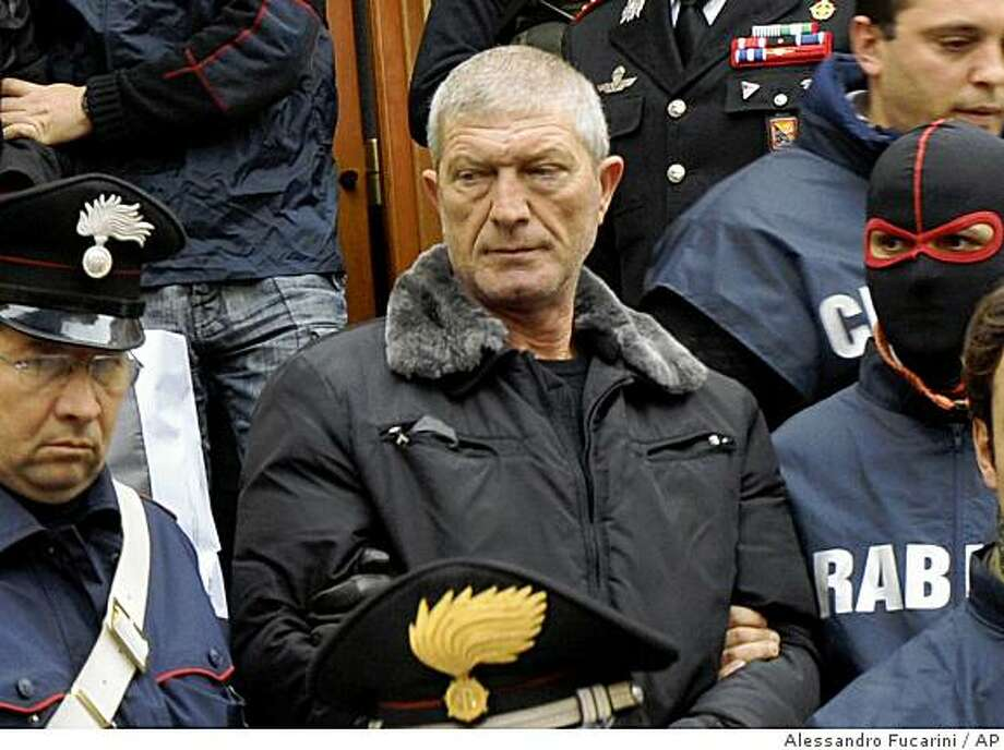 A man identified as Gaetano Lo Presti, center, is escorted by Italian Carabinieri Paramilitary police shortly after his arrest in Palermo, Sicily, Tuesday, Dec. 16, 2008.  Lo Presti, the alleged Mafia boss of a Palermo neighborhood, hanged himself in jail, hours after he was arrested on Tuesday with some other 90 suspects in a blitz against the crime organisation Cosa Nostra, police said on Wednesday Dec. 17, 2008. Authorities had ordered the sweeping raids to prevent what they were mob efforts to rebuild Cosa Nostra. (AP Photo/Alessandro Fucarini) Photo: Alessandro Fucarini, AP