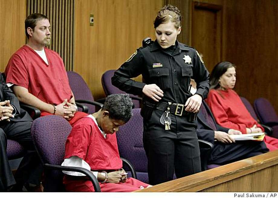 Caren Ramirez, center, Michael Schumacher, left,  Kelly Layne Lau, far right appears in a Stockton, Calif., courtroom on Monday, Dec. 8, 2008.  Investigators say a 16-year-old boy was kept chained in a fireplace, choked with a belt and forced to drink and take drugs during more than a year of captivity in a Northern California home. Schumacher and his wife Kelly Layne Lau and the teen's one-time guardian Ramirez are charged with his torture and kidnapping. (AP Photo/Paul Sakuma) Photo: Paul Sakuma, AP