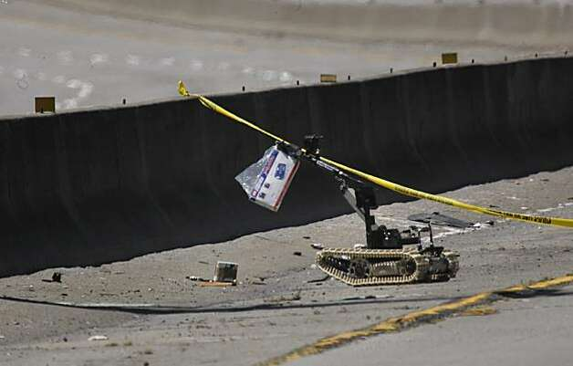 The Alameda County Bomb Squad robot takes a suspicious package to the median of I-580 to be detonated Sunday. Photo: Lacy Atkins, The Chronicle