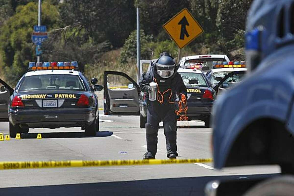 Alameda County Bomb Squad St. Ray Kelly prepares to detonate two suspicious packages from a white Toyota truck on I-580 in Oakland on Sunday, after a shootout Saturday night involving two CHP officers and a man wearing body armor.