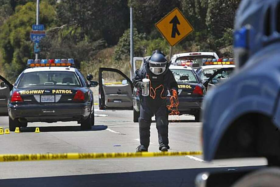 Alameda County Bomb Squad St. Ray Kelly prepares to detonate two suspicious packages from a white Toyota truck on I-580 in Oakland on Sunday, after a shootout Saturday night involving two CHP officers and a man wearing body armor. Photo: Lacy Atkins, The Chronicle