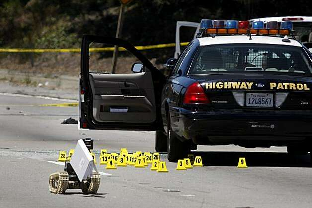The Alameda County Bomb Squad robot takes a handbook from the shootout suspect's truck on I-580 in Oakland on Sunday. Photo: Lacy Atkins, The Chronicle