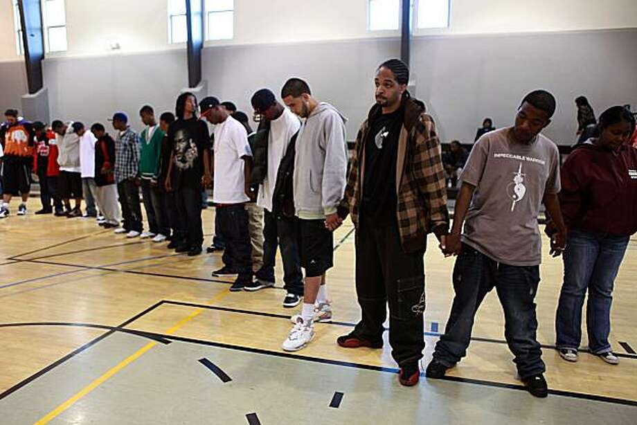 Nate Thomas (checkered jacket) reflects with team members and the community as they hold hands before practice at Joseph Lee Recreation Center in San Francisco, Calif., on Thursday, July 22, 2010.  The city is starting its midnight basketball program which has been dormant for four years because of budget cuts. Photo: Liz Hafalia, The Chronicle