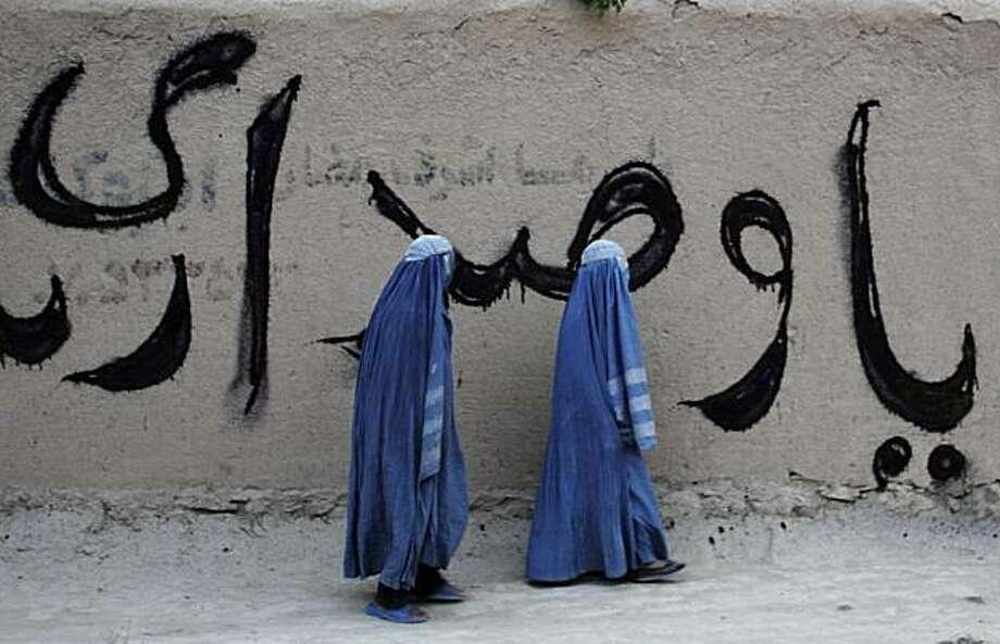 In this photo taken on Thursday, July 22, 2010, Afghan women pass by the part of a parliamentary elections graffiti in Mazar-e-Sharif, north of Kabul, Afghanistan. Parliamentary elections are scheduled for this fall. Photo: Mustafa Najafizada, AP