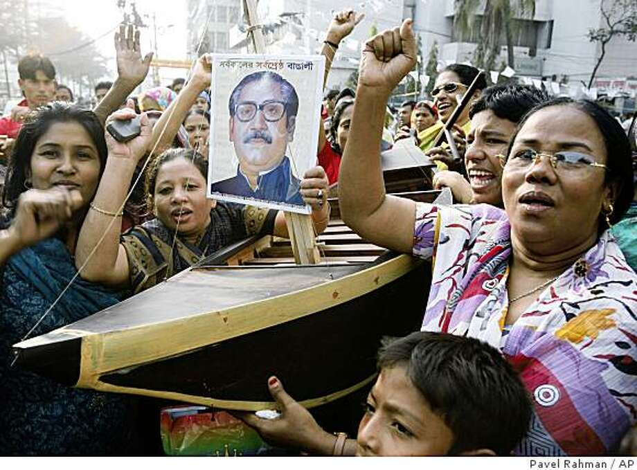 Bangladesh Awami League party activists shout slogans as they carry the photograph their party president Sheikh Hasina's father Sheikh Mujibur Rahman, along with party's election symbol, boat during an election campaign rally in Dhaka, Bangladesh, Monday, Dec. 15, 2008. Bangladesh's two main political parties formally began their election campaigns Friday as restrictions on political rallies were lifted ahead of national polls due later this month. (AP Photo/Pavel Rahman) Photo: Pavel Rahman, AP