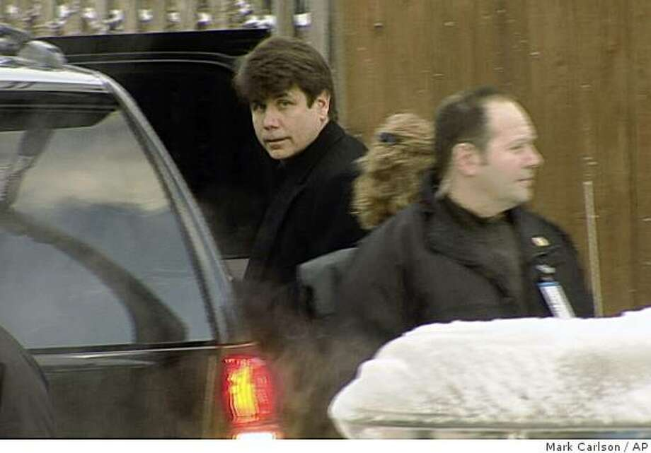 Illinois Gov. Rod Blagojevich, center, leaves his home through a back alley Wednesday, Dec. 10, 2008, a day after he was arrested on federal corruption charges. (AP Photo/Mark Carlson) Photo: Mark Carlson, AP