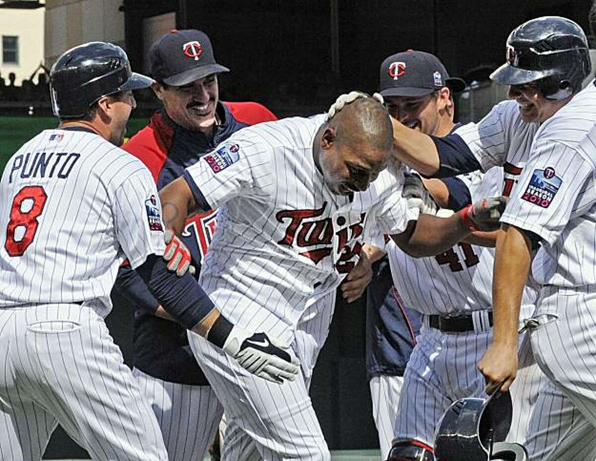 Minnesota Twins' Delmon Young, center, is mobbed after he drove in the winning run off Chicago White Sox pitcher Sergio Santos in the ninth inning of a baseball game Sunday, July 18, 2010, in Minneapolis. The Twins won 7-6. At left is Nick Punto.