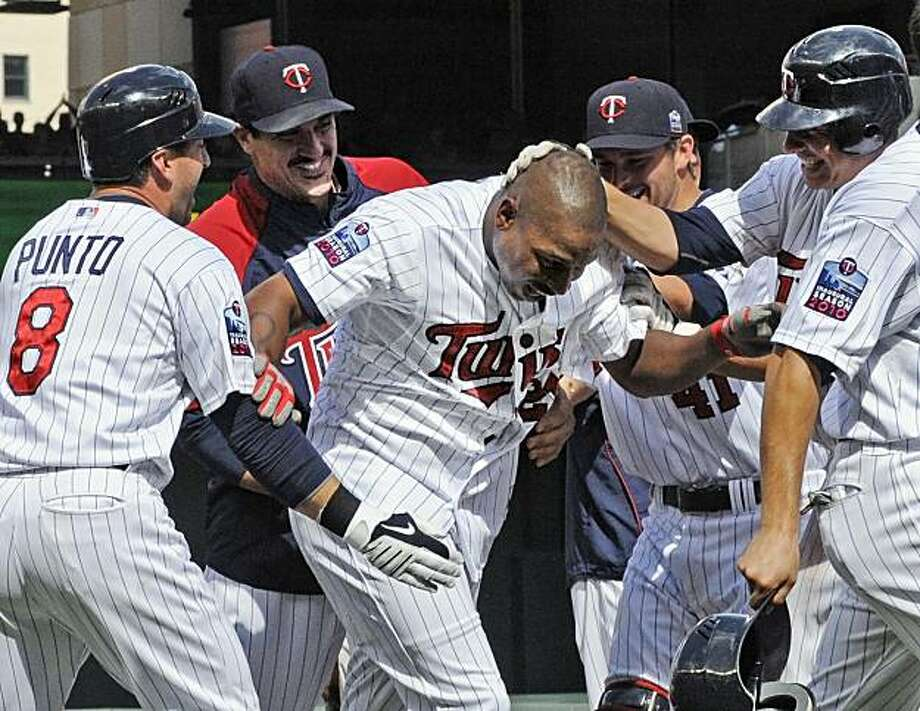 Minnesota Twins' Delmon Young, center, is mobbed after he drove in the winning run off Chicago White Sox pitcher Sergio Santos in the ninth inning of a baseball game Sunday, July 18, 2010, in Minneapolis. The Twins won 7-6. At left is Nick Punto. Photo: Jim Mone, AP