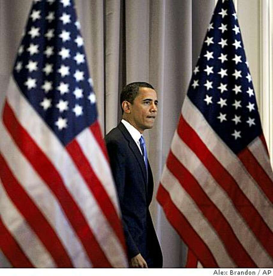 Democratic presidential hopeful Sen. Barack Obama D-Ill., walks between two American Flags to a news conference in Chicago, Wednesday, March 12, 2008.(AP Photo/Alex Brandon) Photo: Alex Brandon, AP