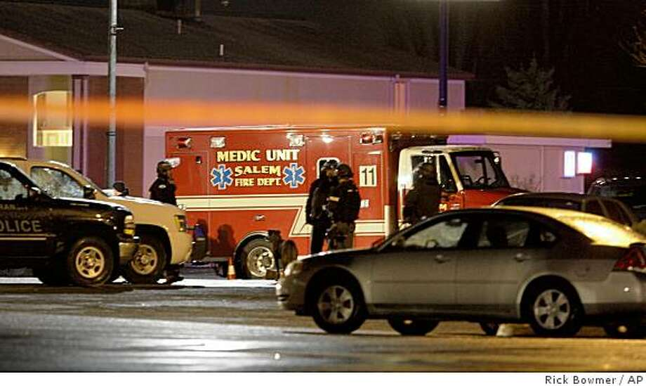 "Rescue workers set up near West Coast Bank where Oregon State Police said a bomb detonated after police arrived to inspect a suspicious device Friday Dec. 12, 2008, in Woodburn, Ore.  Newspaper reports said at least one bomb technician and two bank employees were hurt in the Friday night blast  The Oregon State Police said there were ""serious injuries."" (AP Photo/Rick Bowmer) Photo: Rick Bowmer, AP"