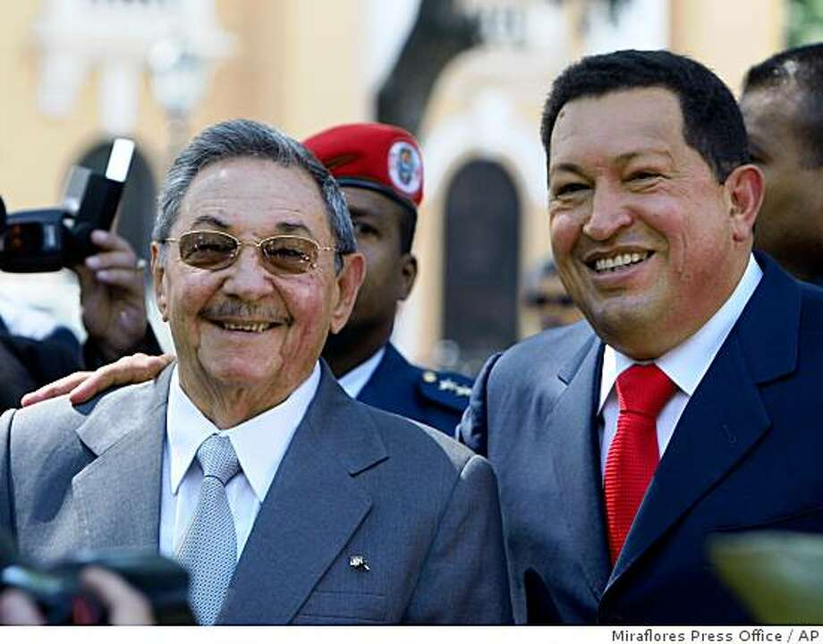 In this photo released by Miraflores Press Office, Venezuela's President Hugo Chavez, right, and Cuba's President Raul Castro smile during a wreath-laying ceremony at the Simon Bolivar square in Caracas, Saturday, Dec. 13, 2008. Castro is in Venezuela on his first international visit as Cuba's leader. (AP Photo/Miraflores Press Office) Photo: Miraflores Press Office, AP