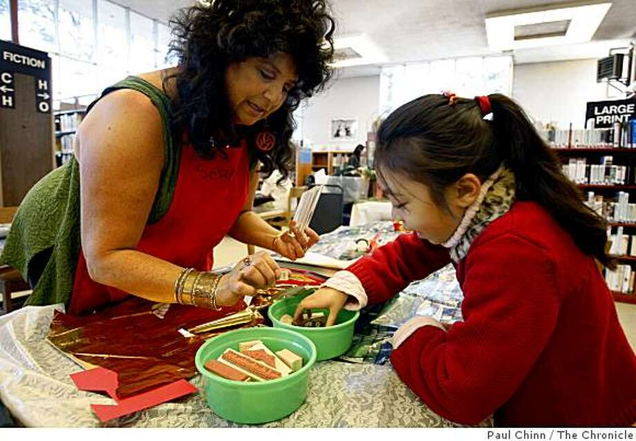 Jane Schafgans helps Naomi Louie, 7, choose a rubber stamp to decorate a greeting card at the Ring in the Green workshop in San Francisco, Calif., on Saturday, Dec. 6, 2008. The event, hosted by the Ortega branch public library, educated participants in eco-friendly approaches to holiday wrapping and greeting cards. Photo: Paul Chinn, The Chronicle