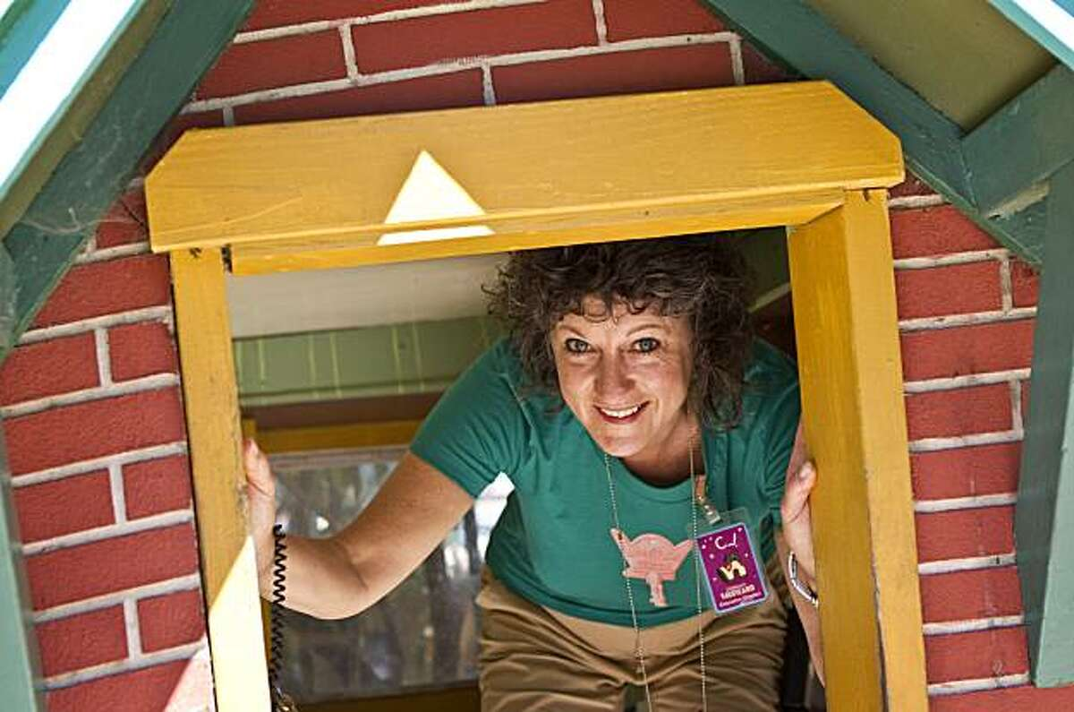 """Children's Fairyland Executive Director Hirschfield peeks out of the """"3 Little Pigs'"""" set in Fairyland in Oakland, Calif., on Thursday, July 15, 2010. Children's Fairyland opened in 1950 and was America's first storybook theme park."""