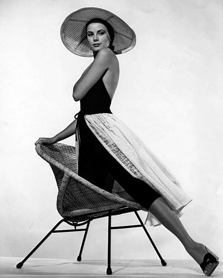 """Graceful Grace Kelly wears a beach outfit designed especially for her latest movie. The black halter suit, with toreador pant, is topped by a loosely woven white apron skirt which can double as a cape. Grace wears the ensemble in """"To Catch A Thief"""". Chief studio designer Edith Head created it. Image taken in Paris, France, 1955. (AP Photo/HO/Str) Photo: Handout/STR, AP"""