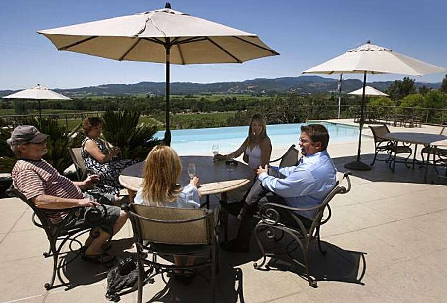 Ryan Shenk (right) hosts visitors on the expansive patio at the Signorello Estate winery tasting room in Napa, Calif., on Thursday, July 8, 2010. Photo: Paul Chinn, The Chronicle