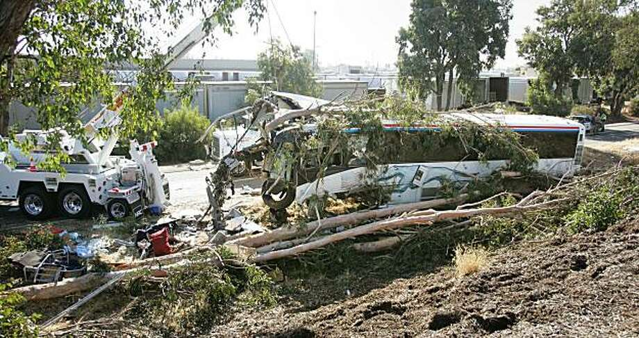 A crane begins to pull a Greyhound Bus that crashed on Highway 99 and killed at least 6 people and injuring manyThursday, July 22, 2010 in Fresno, Calif. Photo: Gary Kazanjian, AP