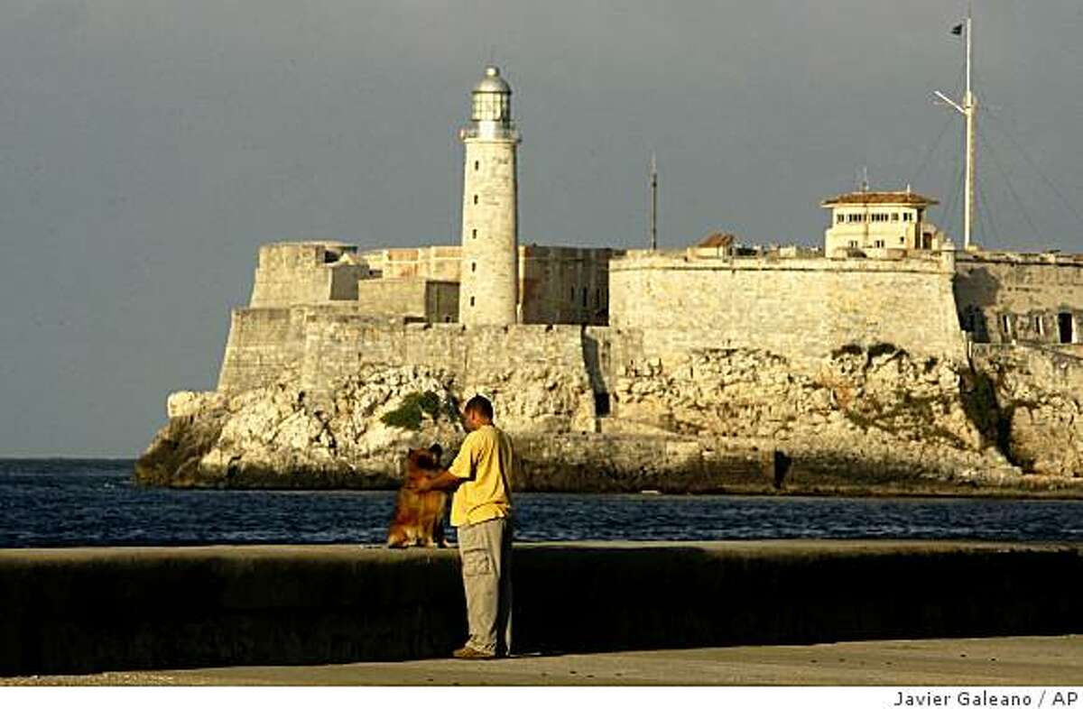 A man walks his dog at the Malecon in Havana, Monday, Nov. 24, 2008. Cuban resorts are gearing up for a record year even as other Caribbean islands lay off workers and suspend construction. The country is booked, thanks to the financial crisis going easy on Canada, its top source of visitors, cheap travel packages and a government that made hotel repairs a priority after three devastating hurricanes.(AP Photo/Javier Galeano)