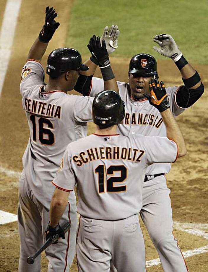 San Francisco Giants' Juan Uribe, upper right, celebrates his grand slam with teammates Edgar Renteria (16) and Nate Schierholtz (12) against the Arizona Diamondbacks during the seventh inning of a baseball game Saturday, July 24, 2010, in Phoenix. Photo: Matt York, AP