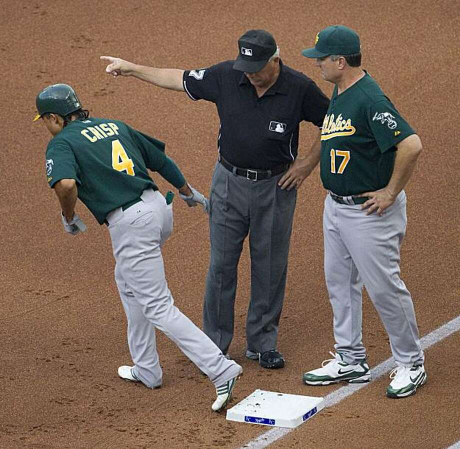 First base umpire Larry Vanover motions Oakland Athletics' Coco Crisp (4) to second after manager Bob Geren (17) appealed Crisp's hit during the first inning of a baseball game against the Kansas City Royals Friday, July 16, 2010 in Kansas City, Mo. The double was originally called a foul ball before the appeal. Photo: Charlie Riedel, AP