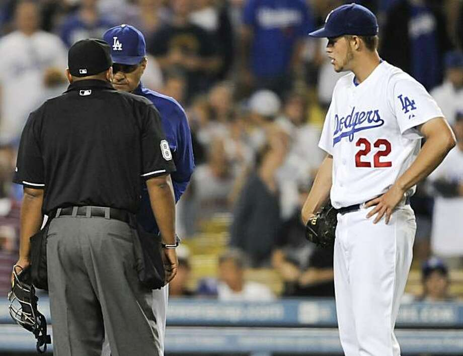 Los Angeles Dodgers manager Joe Torre, back center, talks with home plate umpire Adrian Johnson after ejecting Los Angeles Dodgers starting pitcher Clayton Kershaw (22) in the seventh inning of a baseball game against the San Francisco Giants, Tuesday, July 20, 2010, in Los Angeles. Photo: Gus Ruelas, AP