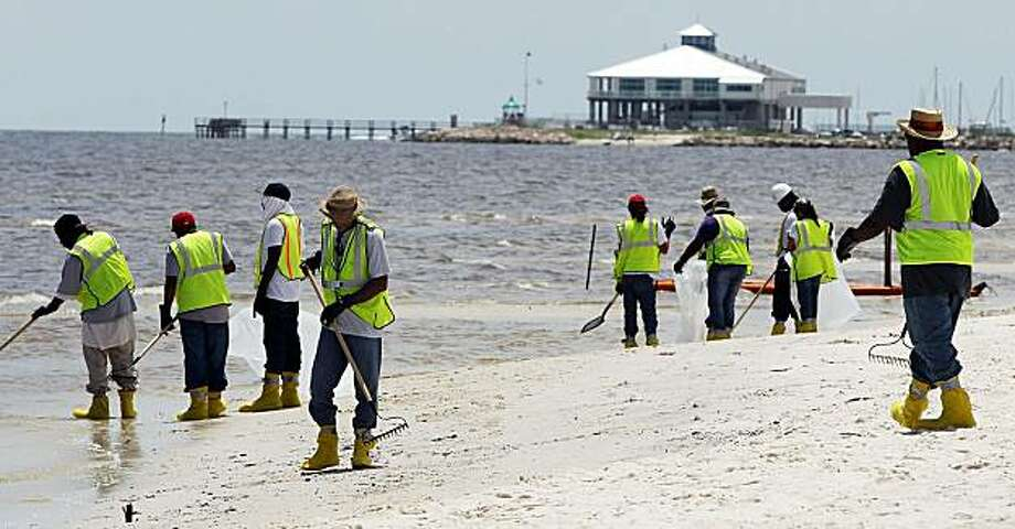 PASS CHRISTIAN, MS - JULY 20:  Workers clean tarballs from a beach July 20, 2010 in Pass Christian, Mississippi. Scientists are concerned that the leaking BP well cap is possibly an indication that the oil well is buckling. Photo: Mario Tama, Getty Images