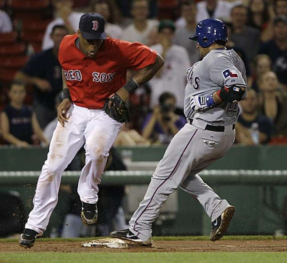Texas Rangers' Bengie Molina, right, beats the throw on a stand-up triple as Boston Red Sox third baseman Adrian Beltre fields the throw during the eighth inning of a baseball game in Boston, Friday, July 16, 2010. Molina hit for the cycle in the game. Photo: Charles Krupa, AP
